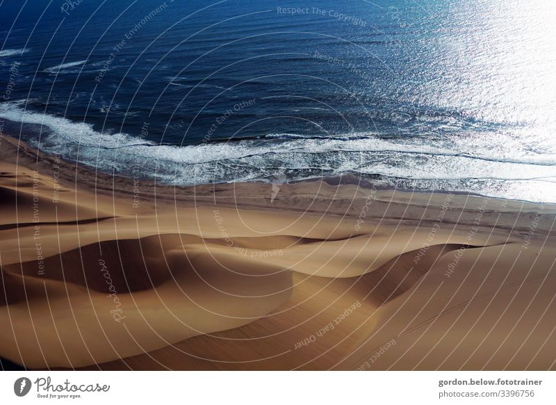 Sand dunes conquer the sea daylight landscape photograph little colour Deserted Shadow Light Water and sand Nature