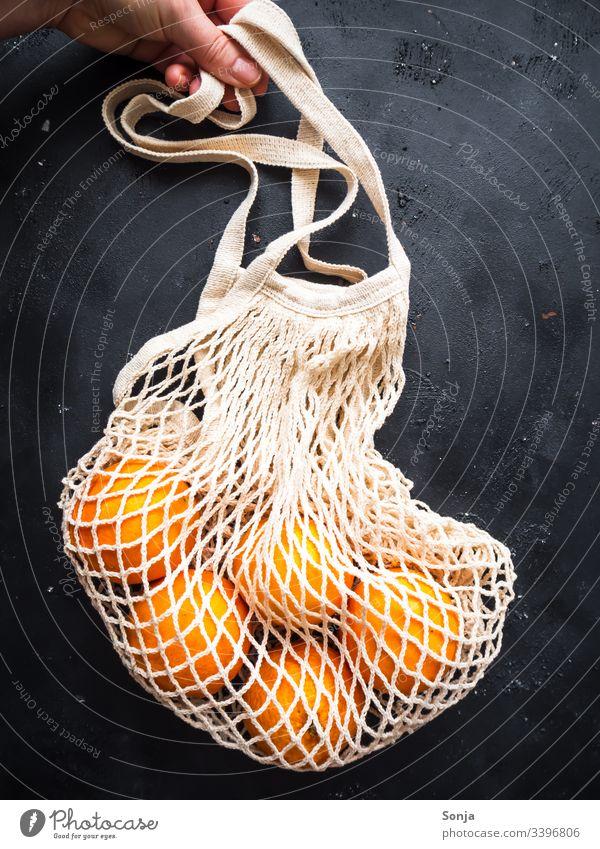 Hand mit einer wiederverwendbaren Einkaufstasche und frischen Orangen auf einem schwarzen Hintergrund einkaufstasche halten Healthy Eating Fruit Food Vitamin