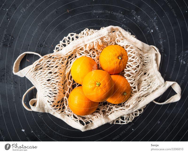 Draufsicht auf frische Orangen in einer wiederverwendbaren Einkaufstasche auf einem schwarzen Hintergrund Frische einkaufstasche draufsicht orange color Fruit