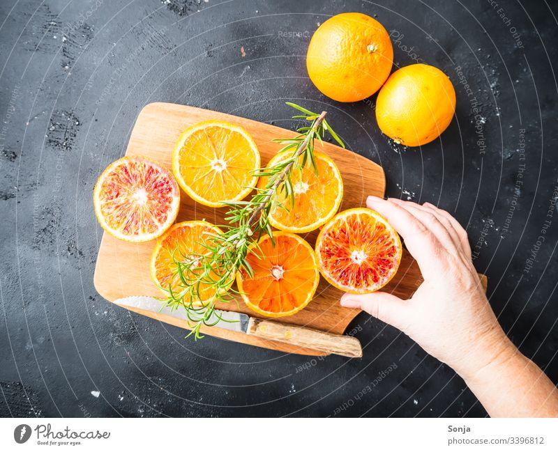 Hand mit frischen halbierten Orangen auf einem Holzschneidebrett auf einem schwarzen Hintergrund hand frau orange holz messer rustikal draufsicht Fruit Arm