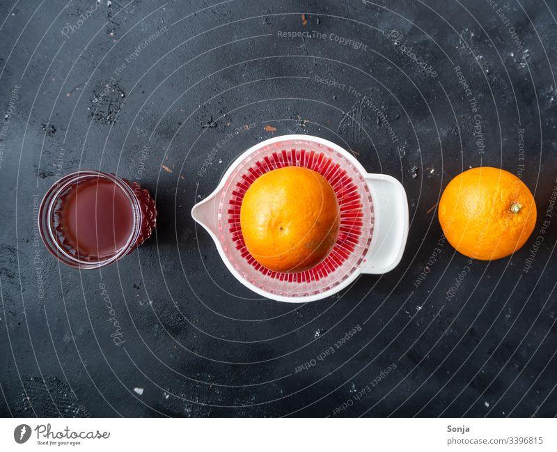 Eine Orange, eine Saftpresse und ein Trinkglas mit Blutorangensaft in einer Reihe auf einem schwarzen Hintergrund, Ansicht von oben saftpresse frischgepresst