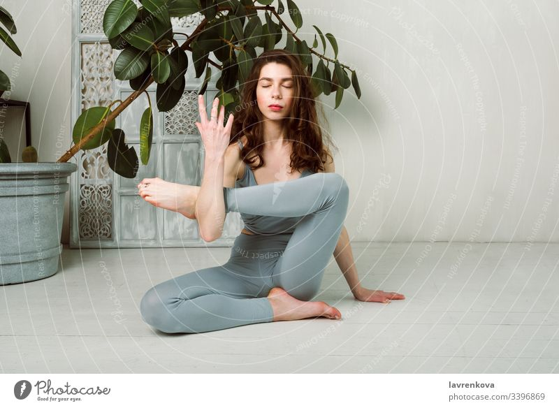 Young yogini practicing on the floor in a room with white walls and plant workout active sport exercise skinny slim leggings brunette calm flexible meditation