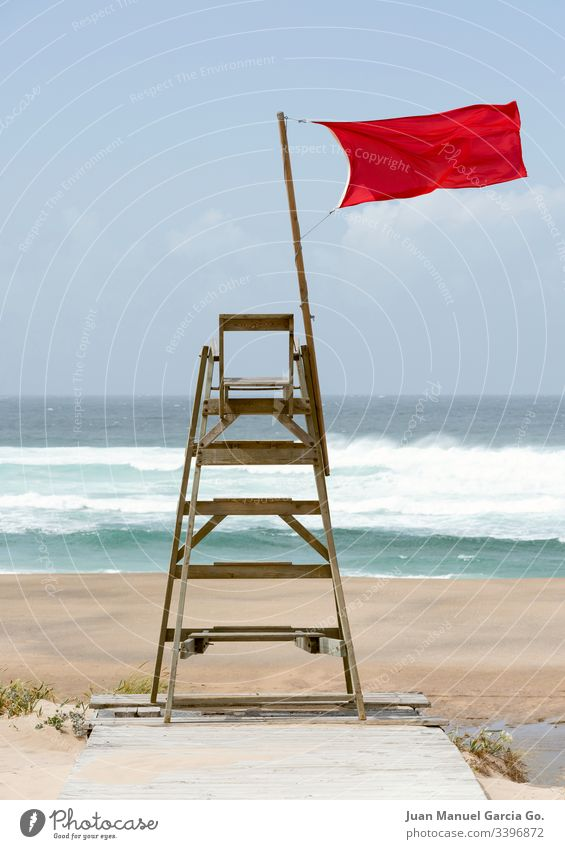 Lifeguard chair sitting empty with a red flag streaming in the wind a coruña aquatic beach blue coast danger drown isolated life lifeguard no people nobody
