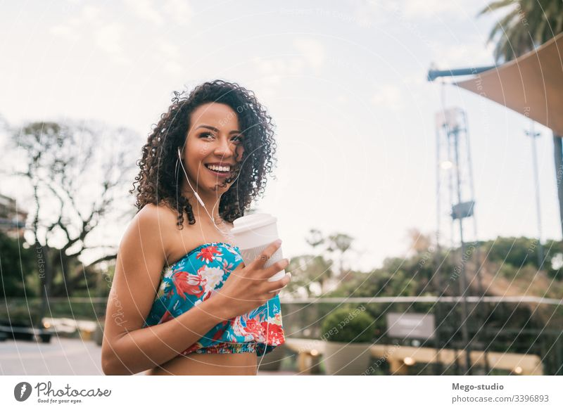 Afro woman listening to music while holding a cup of coffee. coffee cup earphones female afro street ethnicity outside stylish beauty positive relaxing outdoors