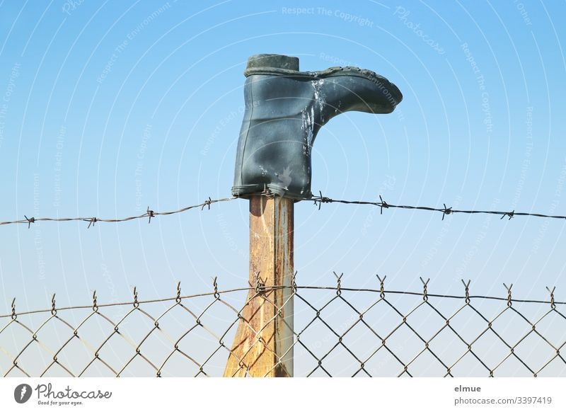 Gumboots on a fence post Rubber boots Boots Fence Barbed wire Sky Bird droppings Inverted Border Blue Protection Barbed wire fence Wire netting fence Deserted
