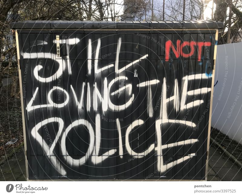 Graffiti on a power box. English r text about the aversion to the police. Police violence Police Force dislike Black Text leap words Youth culture Exterior shot