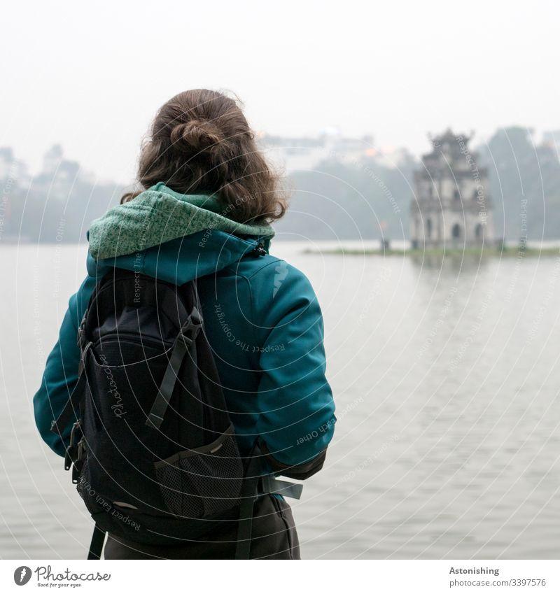 Young woman looks out over Lake Hoan Kiem in Hanoi, Vietnam Hoan Kiem Lake Woman teen Hair Back Rear view Jacket Hooded (clothing) Human being