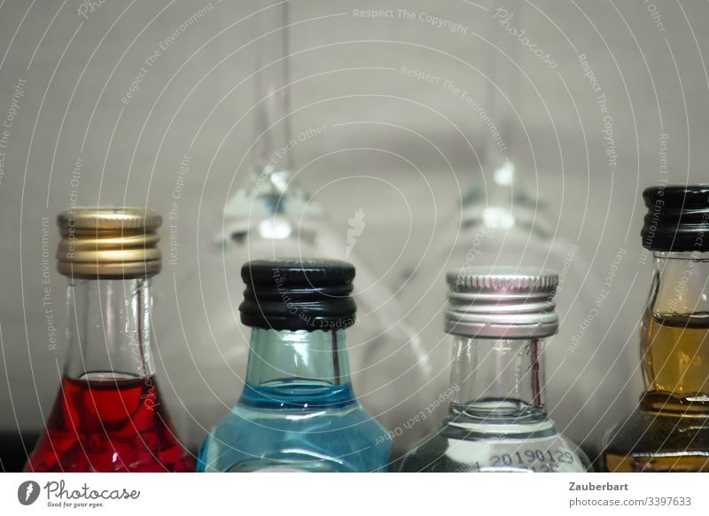 Four bottles of coloured spirits in front of two glasses Liquids Alcoholic drinks Spirits Red Blue Beverage Glass Drinking Minibar Hotel four Close-up