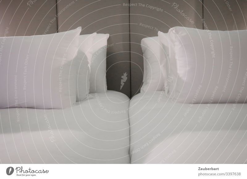 Double bed in a hotel, with white pillows in front of a grey back wall, awaits the travellers Bed Bedclothes Cushion Hotel crack Bedroom Pillow Sheet Sleep