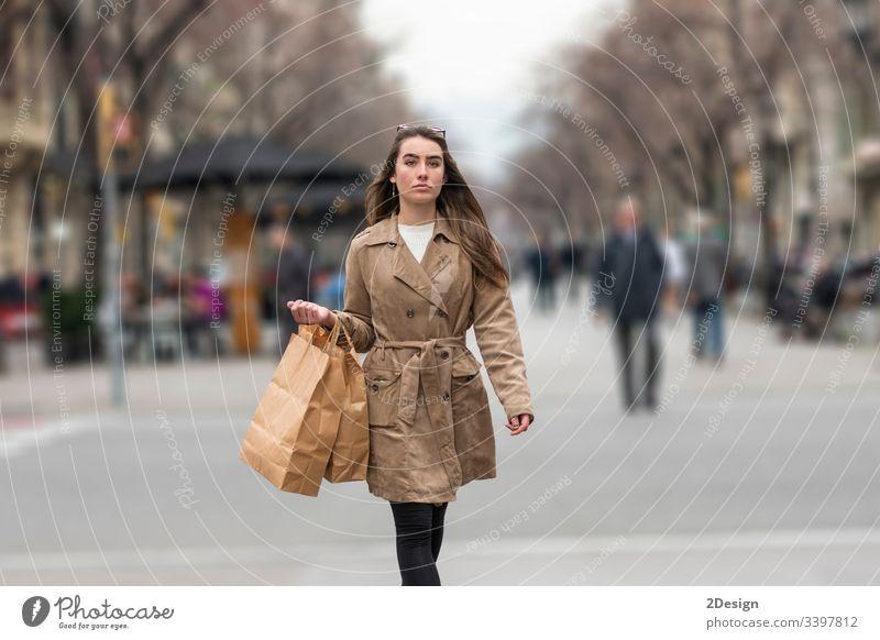 Young woman walking in the street holding shopping handbag teenage mixed race barcelona beautiful fall asian europa happy shopper fashion spain city downtown