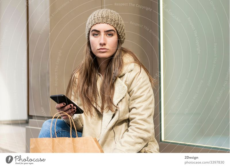 Cute woman sitting outdoors while using a phone 1 lifestyle female mobile phone person adult outside girl street shopping happy smiling people beautiful beauty