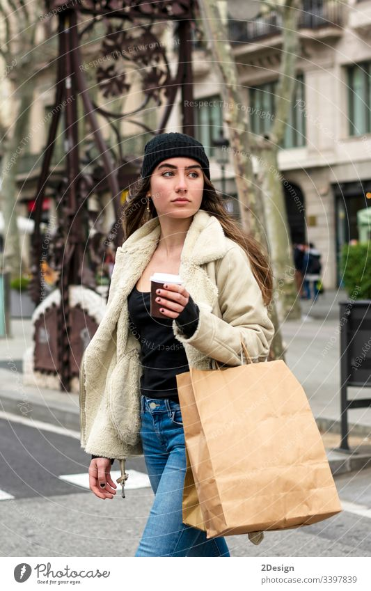Portrait of young european woman walking in a city street, with takeaway coffee in hands modern town alone beautiful cup attractive urban downtown girl stroll