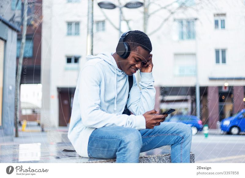 Young Black man sitting on bench while listening music by headphones technology lifestyle male black casual attire trendy happy african earphones guy people