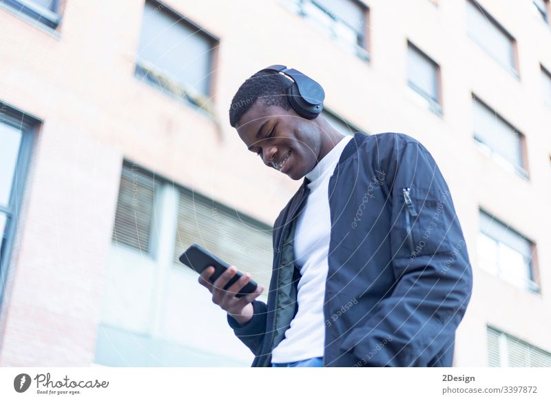 Young Black man standing in the street while listening music by headphones technology lifestyle male black casual attire trendy happy african earphones guy