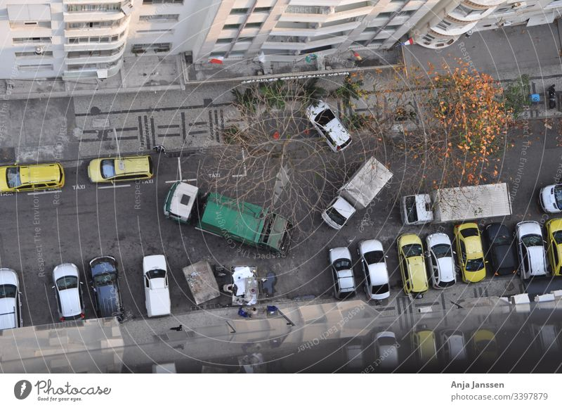 Aerial view of a side street with everyday traffic, garbage collection and parked cars at the roadside in autumn Street secondary roads aerial photograph