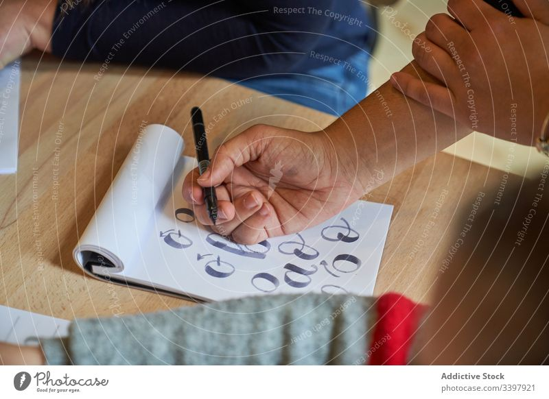 Faceless woman learning lettering at table draw paper handwriting occupation desk workplace art creative craft graphic education notebook skill stationery