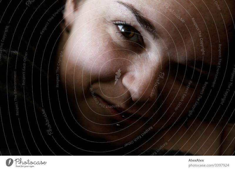 Portrait of a young woman with lip piercing and freckles Forward Portrait photograph Central perspective Shallow depth of field Day Close-up Interior shot