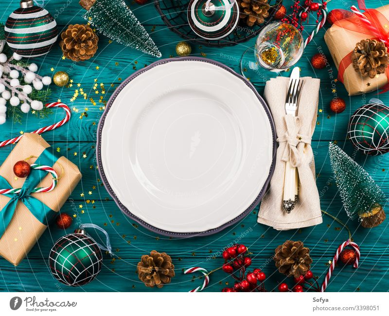 Christmas dark background with empty dish on emerald green wooden table full of festive ornament, gift boxes and candy canes christmas new year dinner holiday