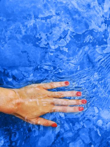 Classic blue color of 2020. Female hand in water classic woman spa harmony red manicure wellness nails nail polish vacation background female trend classical