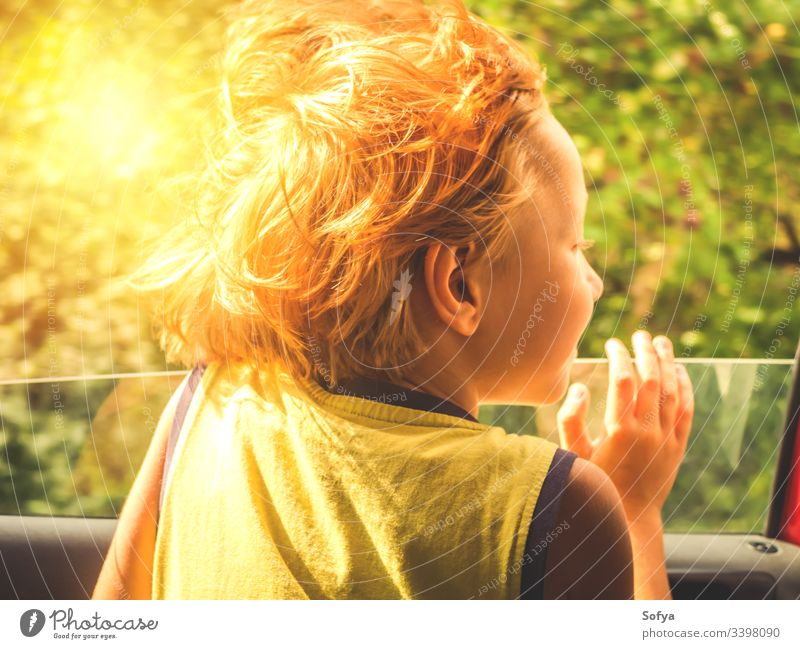 Little boy enjoying sun and wind travelling in a car little child happy skin emotion moment hair summer sunny day light t-shirt yellow blonde caucasian eyes kid