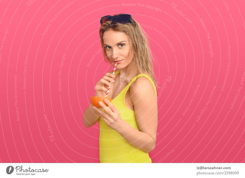 Woman drinking through a straw from an orange attractive beautiful cellulite treatment cheerful cocktail colorful concept conceptual delicious diet expression