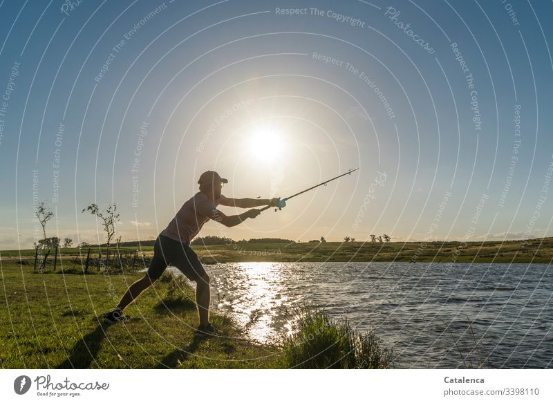 Young man casts a fishing rod on the lake shore, the sun is shining, the water is shining Fishing (Angle) Fisherman Fishing rod Colour photo Coast Food Lake