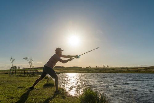Young man casts a fishing rod on the lake shore, the sun is shining, the water is shining Fishing (Angle) Fisherman Fishing rod Colour photo Coast Food Lake