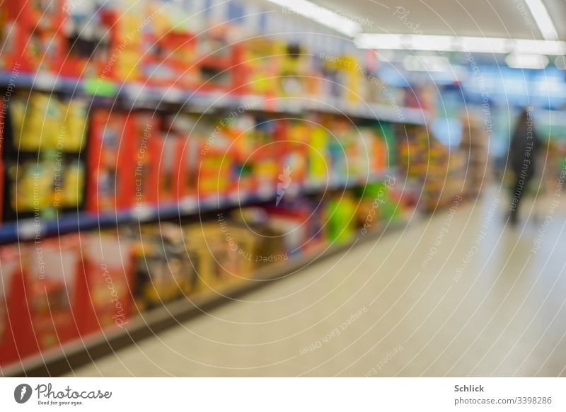 Blurred, colourful, full shelves in the supermarket and customer in the background Supermarket Shelves Customer buyer Consumption consumer motley blurred