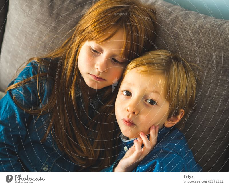 Two blonde little sibling kids on a sofa child smile face hug family love siblings brother sister redhead funny sweet tender together near indoors portrait