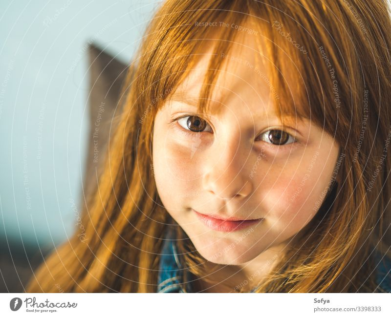 Cute redhead little girl looking at us and smiling cute child vivid eyes young cheerful smile kid hair ginger happy joy enjoy selfconfident face skin freckles