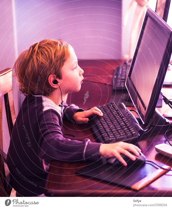 Cute little boy playing at pc concentrated. Purple tone computer child kid technology internet leisure male person lifestyle music modern home caucasian game
