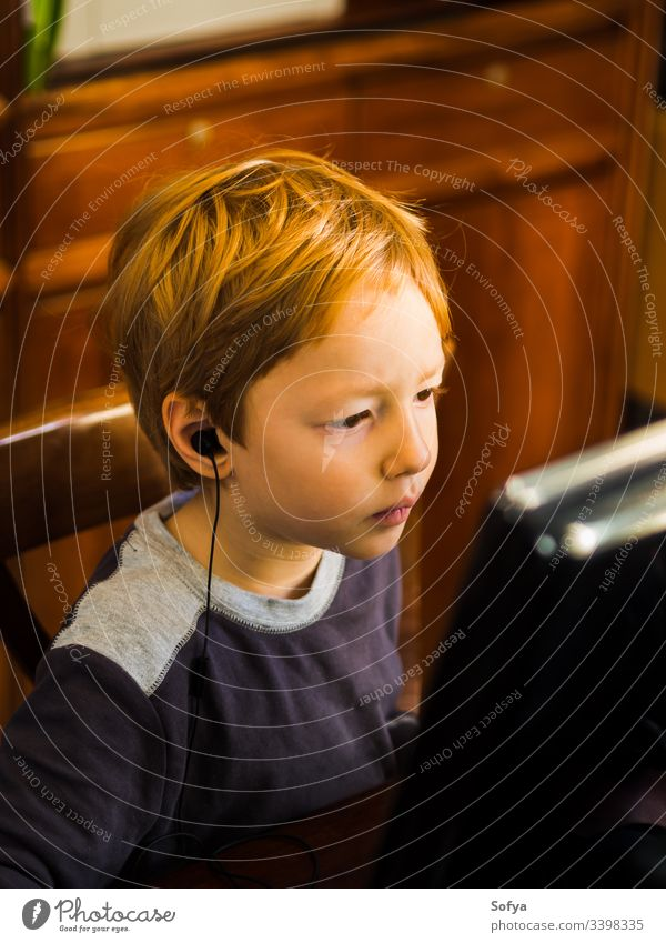 Cute little boy playing at pc with very concentrated face expression computer child kid technology internet leisure male person young lifestyle music modern