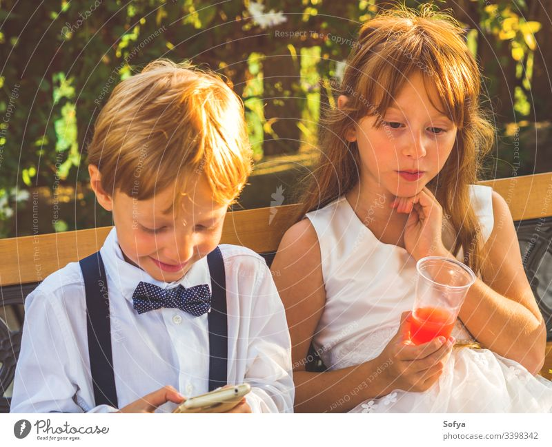 Ring bearer and flower girl relaxing at wedding children technology using smartphone boy happy mobile hang out break ring bearer summer siblings play kid nature