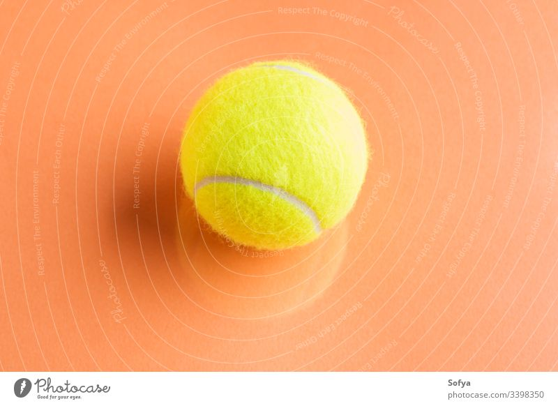 Tennis ball on orange abstract background with reflection. tennis competition concept motion equipment racket sport yellow trendy play teaching game match point