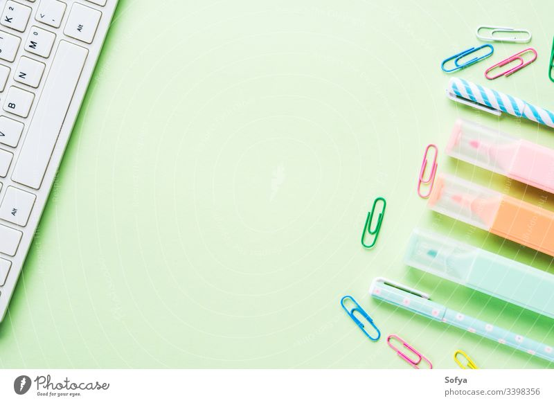 Mint green back to school flat lay concept frame with keyboard, colorful highlighters and clips stationery blogging sneakers blank computer shoes create