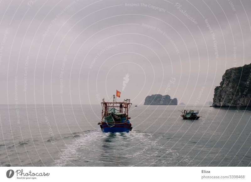 A ship on the sea in Halong Bay in Vietnam; beautiful landscape with limestone rocks rising out of the sea in foggy weather Halong bay Ocean Limestone rocks