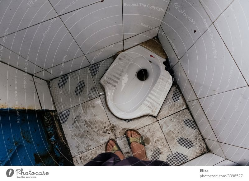 A bird's-eye view of a dirty squatting toilet with female feet on it in Southeast Asia Toilet Crouch unaccustomed john Woman disgusting travel South East Asia