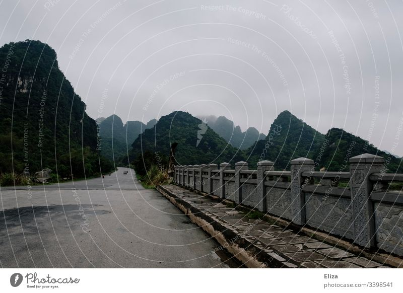 A stone bridge in front of a beautiful mountain landscape with limestone rocks in Ninh Binh, Vietnam Landscape Bridge mountains Street travel Vacation & Travel
