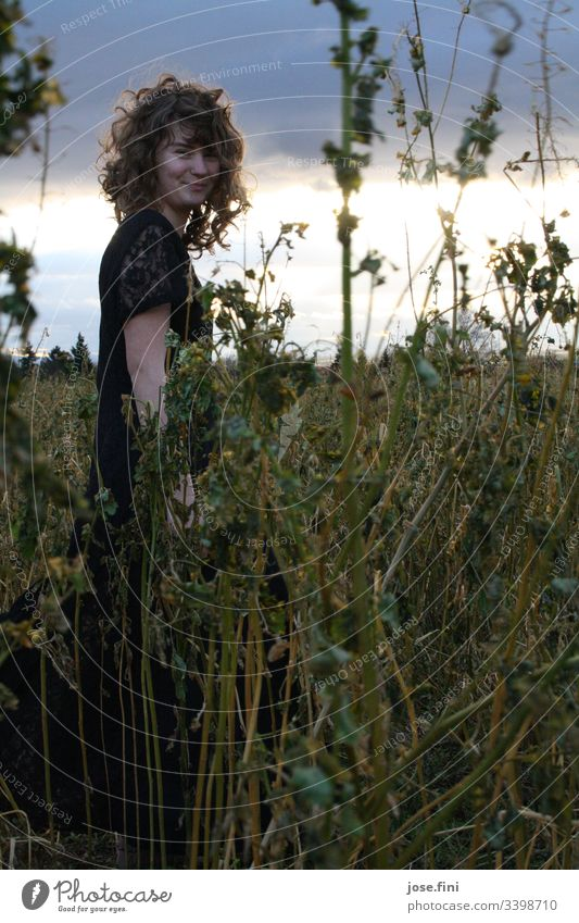 Young woman stands in a high field, in bright sunlight breaking through dark clouds Beautiful Feminine Day Exterior shot Nature Natural Free Light Sunlight