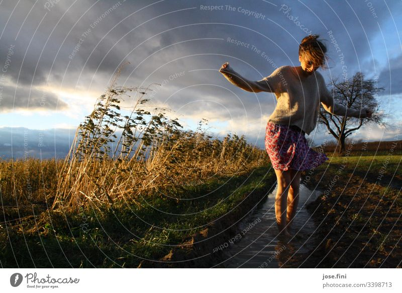 Woman standing in puddle in field Young woman Skirt Feminine Day Field Meadow acre Puddle Clouds Storm clouds windy Nature Landscape Barefoot somber Sunlight