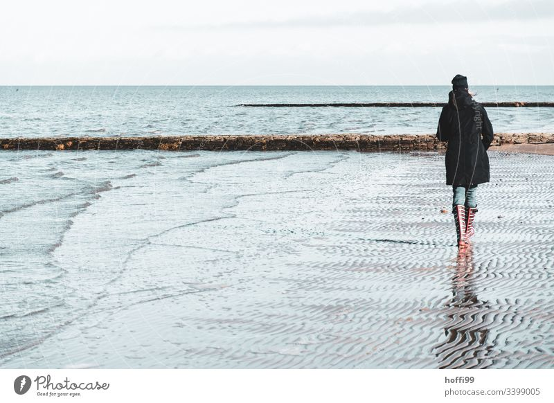Woman with red striped rubber boots walks alone on the beach in winter Rubber boots Red red rubber boots Legs Boots North Sea coast Mud flats watt Landscape