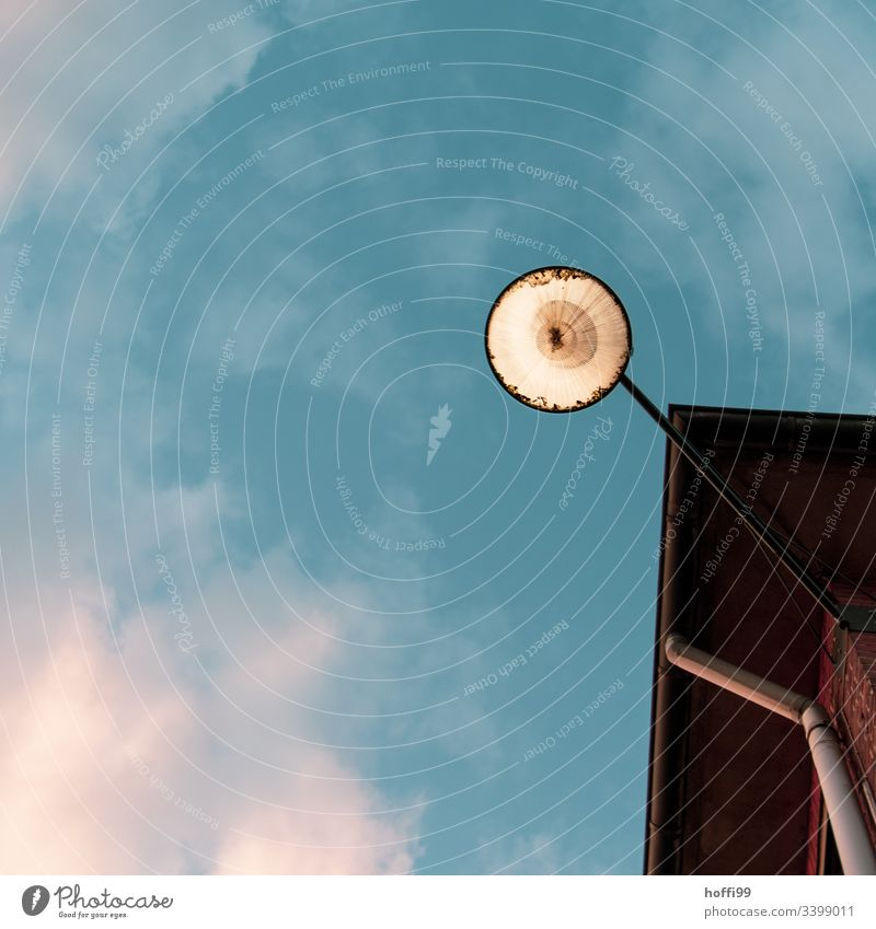 View of a street lamp on the house wall from below against a cloudy sky Minimalistic Lamp Street lighting Lantern Flag flag Blue sky Blue background Summer