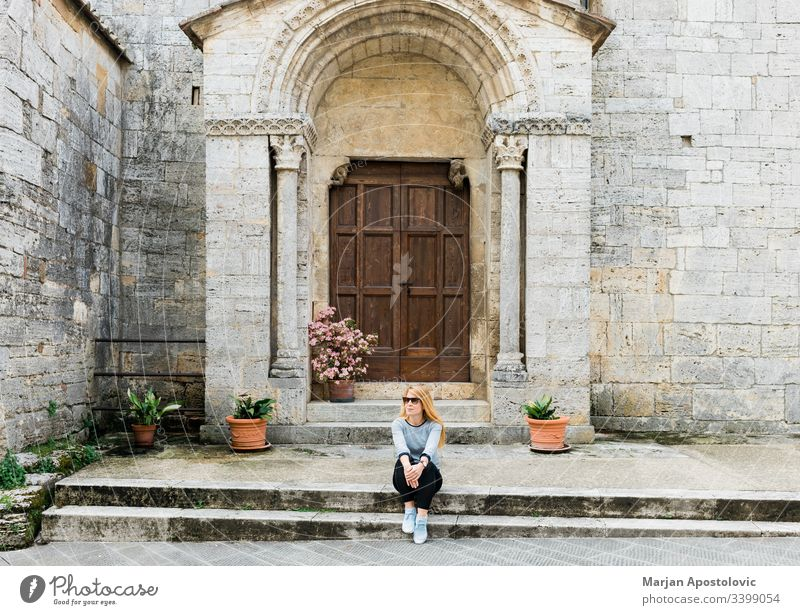 Young female traveler sitting on steps of medieval church in Tuscany, Italy adult ancient antique architecture building casual catholic culture door enjoying