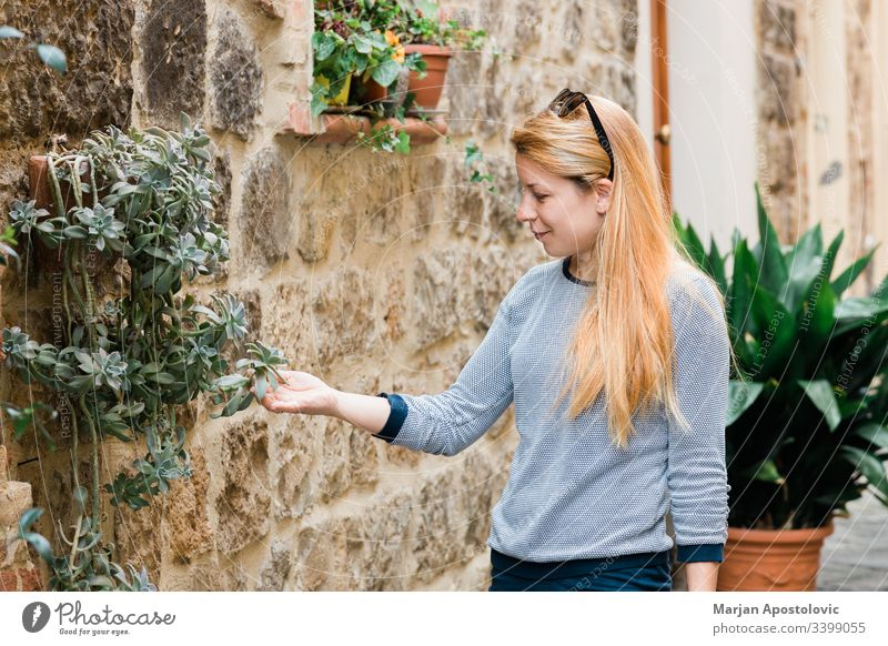 Young female traveler in the streets of an old town in Tuscany, Italy admiring floral decorations on the building alley ancient casual caucasian city enjoying