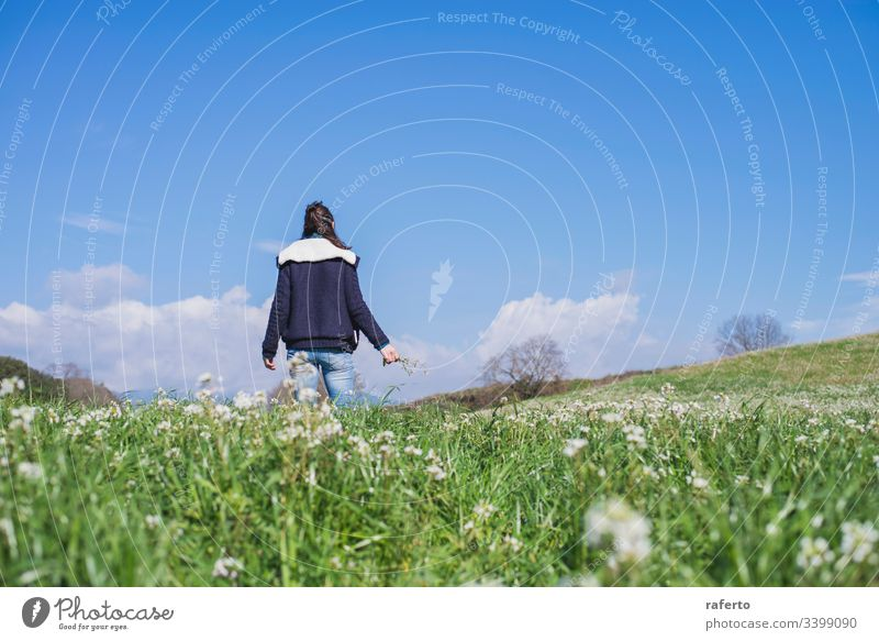 Rear view of a brunette Hispanic woman in casual clothes walking on the field Field Flower Green Back Freedom Spring 1 Woman Nature on one's own Summer