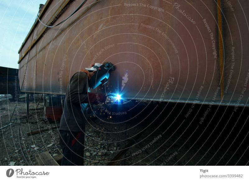 Welder Working in a Shipbuilding Yard assembly construction dock dockworker dockyard heavy industrial industry job laborer maintenance maritime metal nautical
