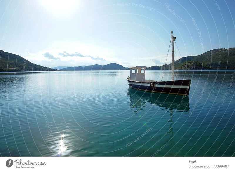 Dark Blue Fishing Boat Anchored in a Bay aegean blue boat calm clouds dark blue island hills meditearranean ocean old peaceful reflection sea shining sky sun