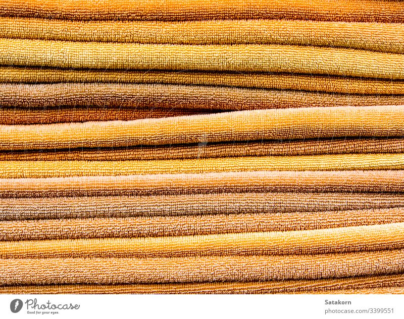 Pile of yellow towels pile stack clean orange color bath laundry background texture soft fabric cotton wipe objects bathroom shower