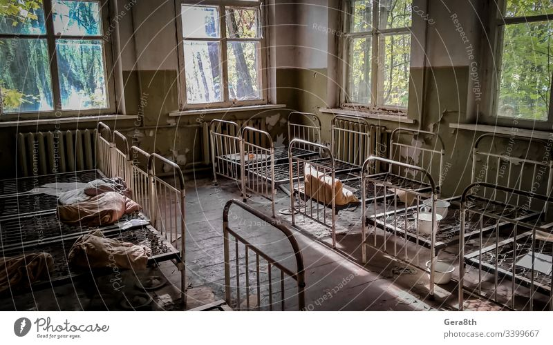 empty children's beds in an abandoned kindergarten house with peeling walls in Chernobyl abandoned house accident building dangerous deserted ecology empty beds