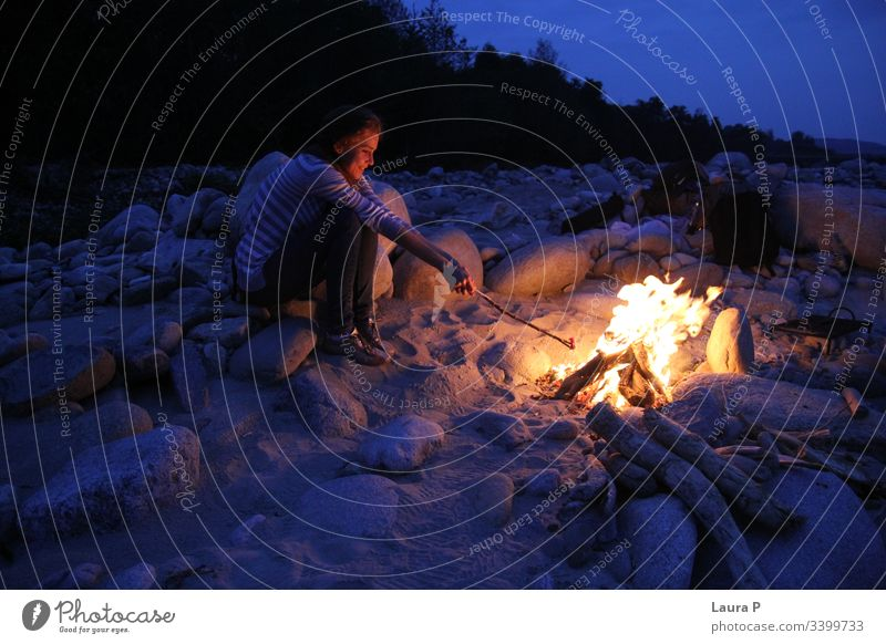 Woman holding a stick next to a camp fire in the evening young woman outside outdoors Camp fire atmosphere Fire Colour photo Exterior shot Hot Night Fireplace